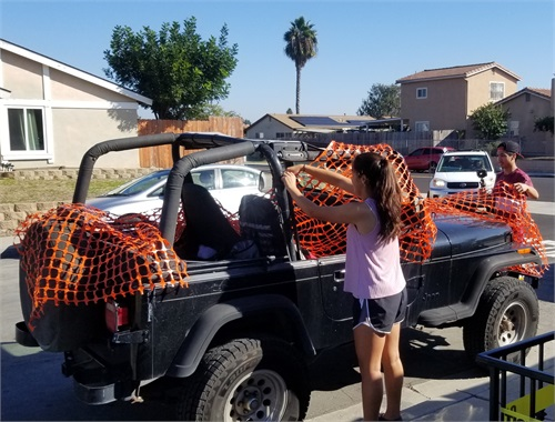 The youngsters try to cover the jeep