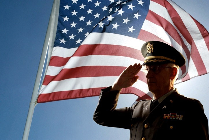 A veteran saluting the United States flag.